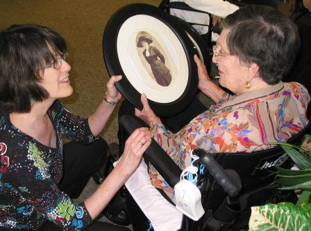 Katz' daughter Mary presents her with an archival photo of Katz' mother for her 95th birthday, 2010
